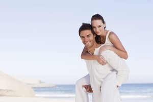 Happy young man giving woman piggyback on beach